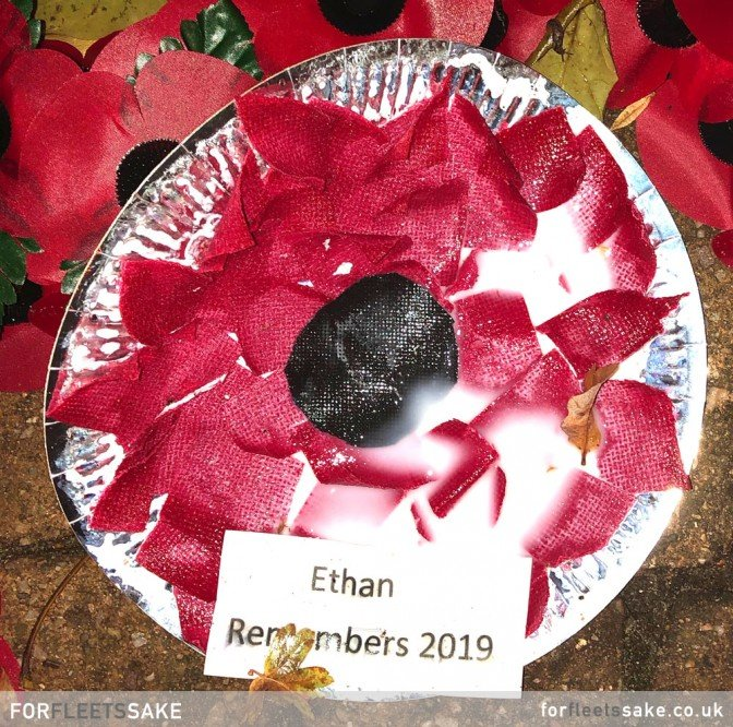 GURKHA SQUARE WAR MEMORIAL DISPLAY 2019. The individual poppy wreaths and crosses than lay bathed in the red glow of the war memorial.