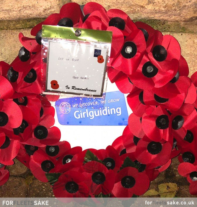 GURKHA SQUARE WAR MEMORIAL DISPLAY 2019. The individual poppy wreaths and crosses that lay bathed in the red glow of the war memorial.